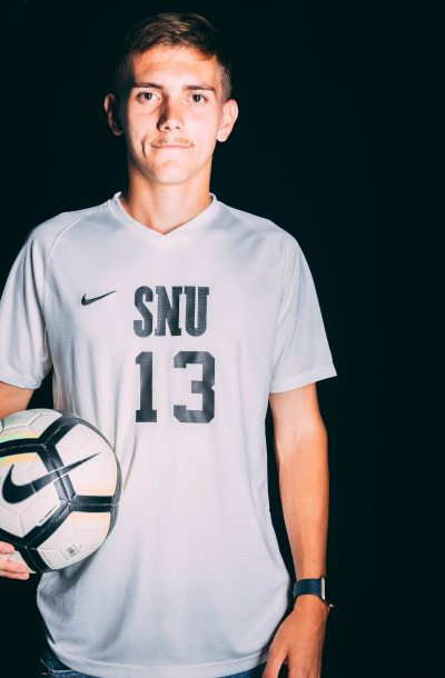 caucasian boy with a white SNU jersey and a soccer ball